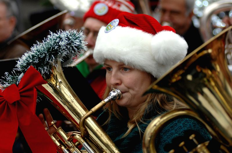 A tuba player performs Christmas carols and songs during the 41st annual Tuba Christmas 2014 event next to the Robson Square ice rink in Vancouver, Canada, ...