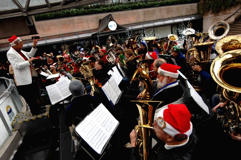 Tenor and bass tuba players perform Christmas carols and songs during the 41st annual Tuba Christmas 2014 event next to the Robson Square ice rink in Vancouver, ..