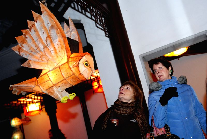 Two women look at a lantern during the 21st annual Winter Solstice Lantern Festival in Vancouver, Canada, on Dec. 21, 2014. Honoring many cultural traditions, the
