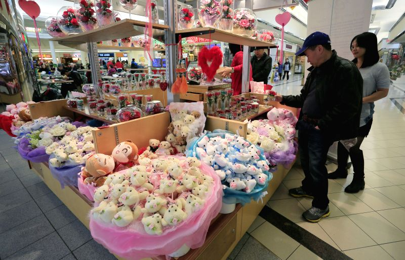 People choose flower decorations at a shopping mall in Vancouver, Canada, Feb. 13, 2015. In celebrating the Valentine's Day, different shops geared up with their .