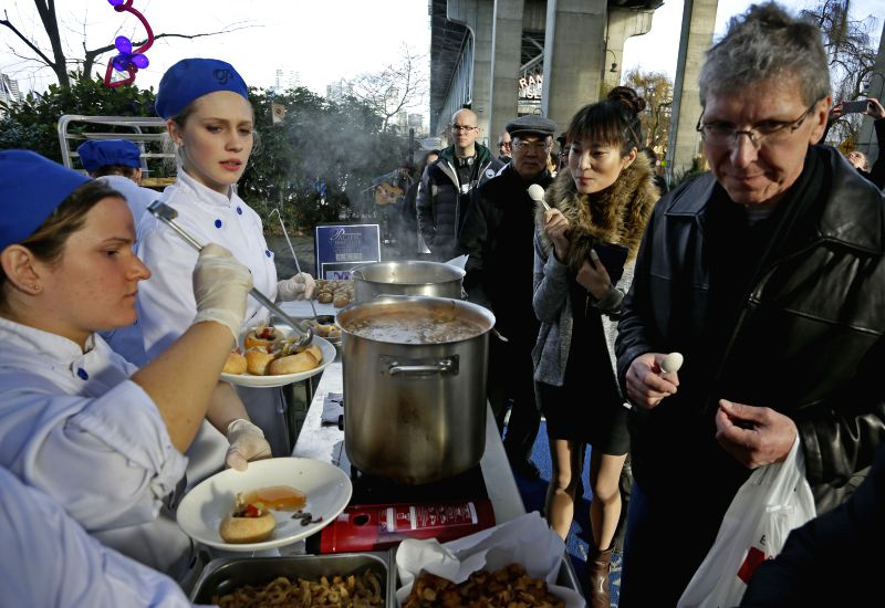 People line up to taste the soup during the Chef Soup Experiment event at Granville Island in Vancouver, Canada, Jan. 16, 2015. The 13th Dine Out Vancouver ...