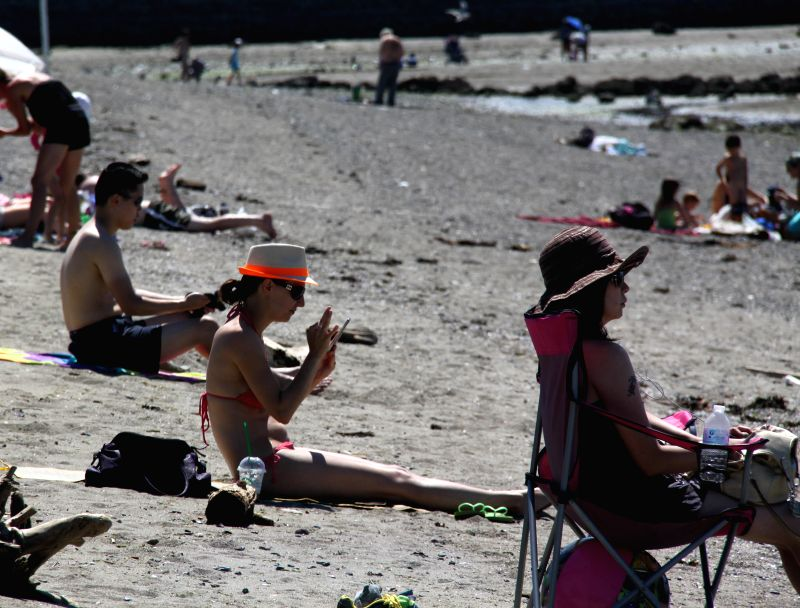 People rest at the seaside in summer in Vancouver, Canada, July 15, 2014.