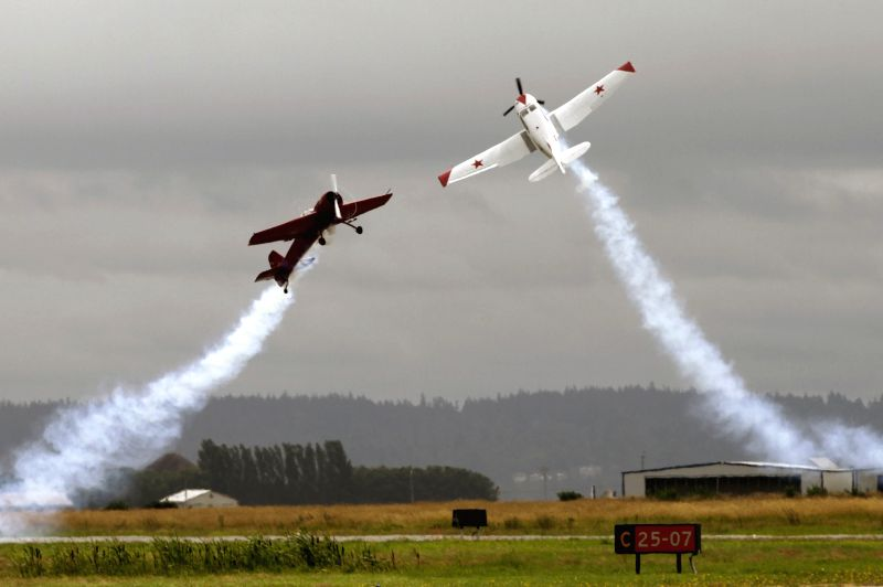 Two aircrafts fly across each other during a performance on the Boundary Bay Air Show in Delta, Canada, July 19, 2014. The 9th Boundary Bay Air Show featured more