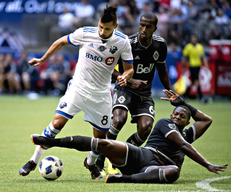 VANCOUVER, July 26, 2018 - Montreal Impact Saphir Taider (L) and Vancouver Whitecaps Doneil Henry compete for the ball during the semifinal matches of the Canadian Championship at BC Place in ...