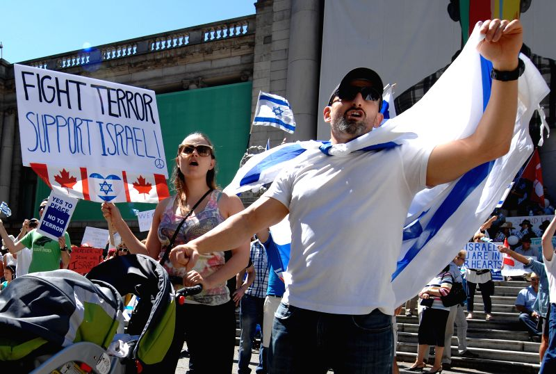 A couple shouts slogans during the pro-Israel rally in Vancouver, Canada, July 27, 2014. Thousands of people rallied in Vancouver Sunday to support Israel's ...