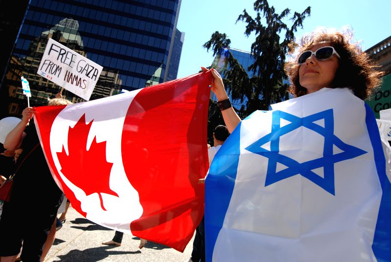 People hold national flags of Israel and Canada during the pro-Israel rally in Vancouver, Canada, July 27, 2014. Thousands of people rallied in Vancouver Sunday ..