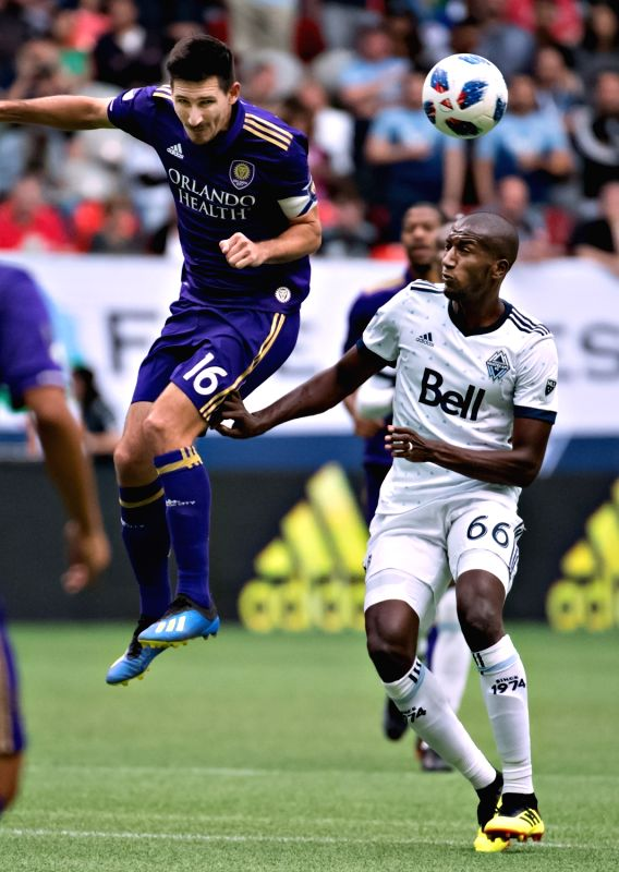 VANCOUVER, June 10, 2018 - Aly Ghazal (R) of Vancouver Whitecaps vies with Sacha Kljestan of Orlando City SC during a regular season MLS match at BC Place in Vancouver, June, 9, 2018. The Vancouver ...
