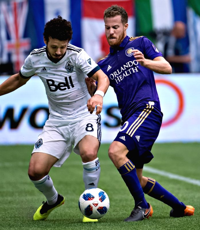 VANCOUVER, June 10, 2018 - Felipe Martins (L) of Vancouver Whitecaps vies with Oriol Rosell of Orlando City SC during a regular season MLS match at BC Place in Vancouver, June, 9, 2018. The Vancouver ...