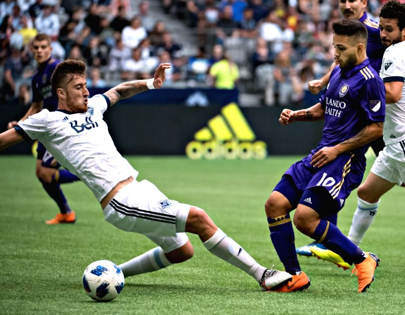 VANCOUVER, June 10, 2018 - Jpose Aja (L) of Vancouver Whitecaps vies with Josue Colman of Orlando City SC during a regular season MLS match at BC Place in Vancouver, June, 9, 2018. The Vancouver ...