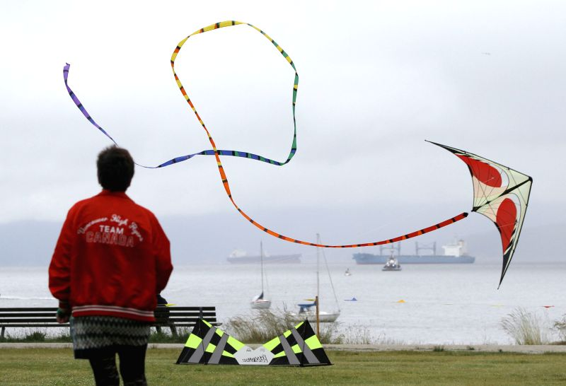 A woman flies a kite at the 39th Pacific Rim kite festival in Vancouver, Canada, June 15, 2014. Dozens of kite enthusiasts participate in the 39th annual Pacific .