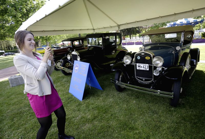 A visitor takes photos of vintage cars at the Collector Car Show in Vancouver, Canada, June 20, 2014. The second annual Collector Car Show and Auction showcases ..
