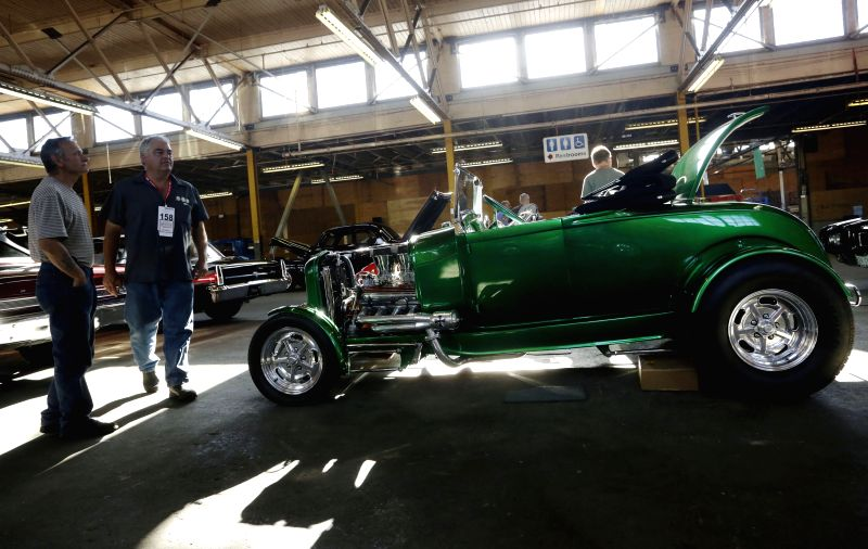 Visitors look at a rebuilt vintage car at the Collector Car Show in Vancouver, Canada, June 20, 2014. The second annual Collector Car Show and Auction showcases ..
