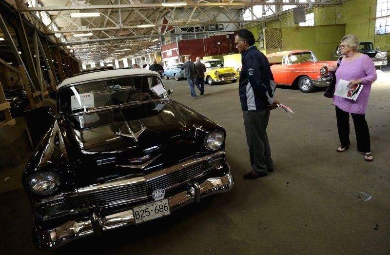 Visitors look at an vintage racing car at the Collector Car Show in Vancouver, Canada, June 20, 2014. The second annual Collector Car Show and Auction showcases ..