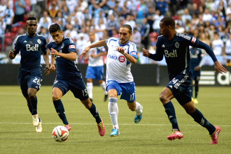 Vancouver Whitecaps' Carlyle Mitchell (1st R) vies with Montreal Impact's Issey Nakajima-Farran (2nd R) during their MLS soccer match at BC Place in Vancouver, ...