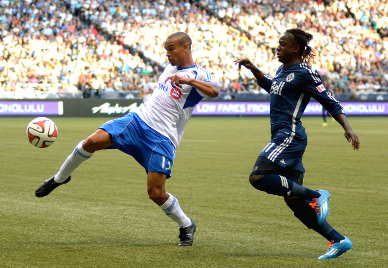 Vancouver Whitecaps' Darren Mattocks (R) vies with Montreal Impact's Matteo Ferrari during their MLS soccer match at BC Place in Vancouver, Canada, on June 25, ...