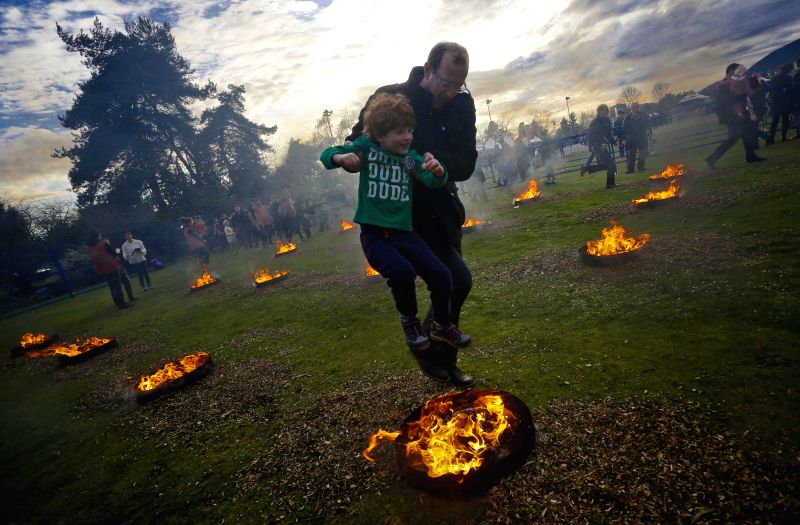 A parent helps his child leaping over a bonfire during Nowruz festival at Ambleside Park, West Vancouver , Canada, March 17, 2015. Hundreds of the Iranian ...
