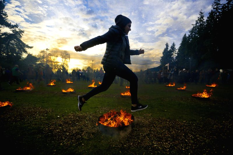 A resident leaps over a bonfire during Nowruz festival at Ambleside Park, West Vancouver , Canada, March 17, 2015. Hundreds of the Iranian residents participated ...