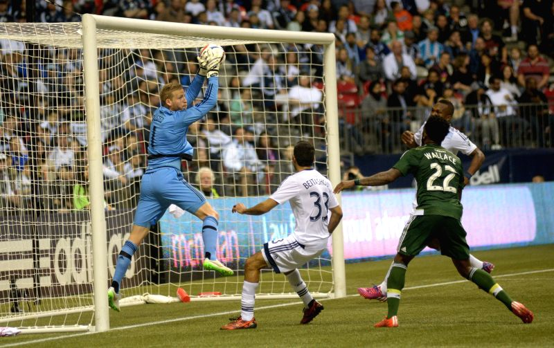 Vancouver Whitecaps' goalkeeper David Ousted (L) makes a save against Portland Timbers during their MLS soccer game at BC Place in Vancouver, Canada, on March ...