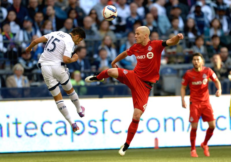 Vancouver Whitecaps' Matias Laba (L) vies with Toronto FC' Michael Bradley during their MLS soccer match at BC Place in Vancouver, Canada, March 7, 2015. Toronto ...
