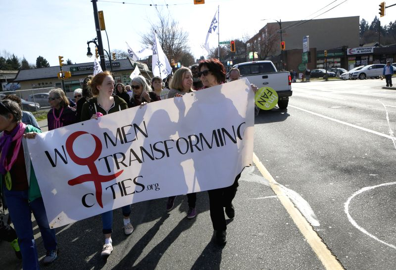 Participants hold a banner during the parade marking the International Women's Day in Vancouver, Canada, on March 8, 2015. Around 200 women participated in the ...