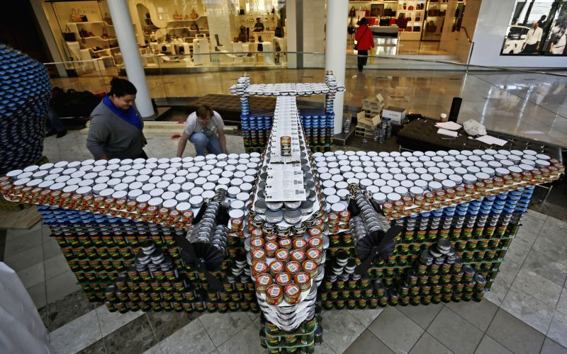 """Participants work on an aeroplane-shaped canned food sculpture during the """"Canstruction"""" competition in Vancouver, Canada, May 11, 2014. The Vancouver ..."""