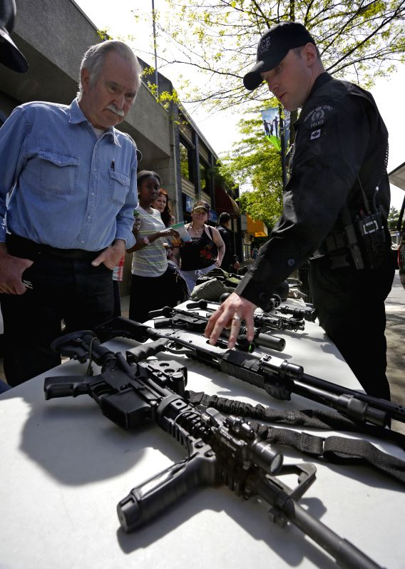Residents look at different kinds of guns used by police special task force during the open house event at a police office in Surrey Vancouver, Canada, May 14, ...