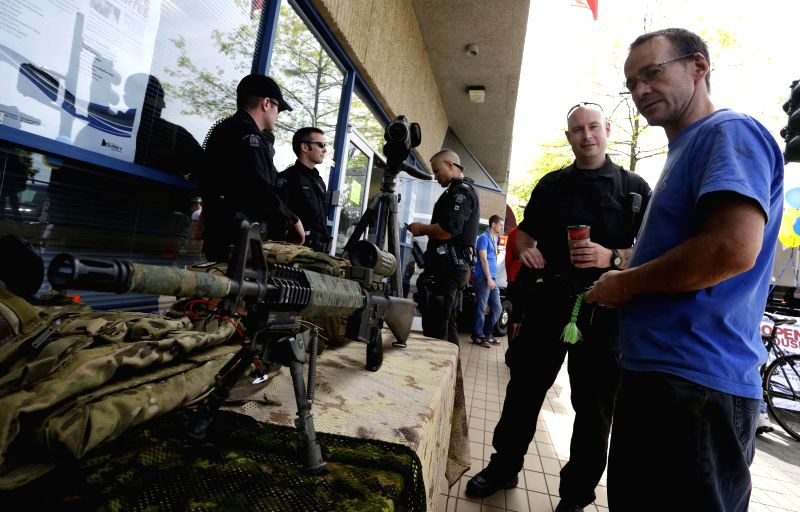 Residents look at some police equipment during the open house event at a police office in Surrey Vancouver, Canada, May 14, 2014. In celebration of the National ...