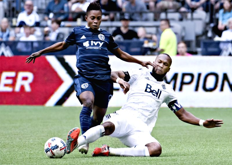 VANCOUVER, May 21, 2017 - Sporting Kansas City's Latif Blessing (L) and Vancouver Whitecaps Kendall Waston compete for the ball during a MLS soccer game in Vancouver May, 20, 2017.