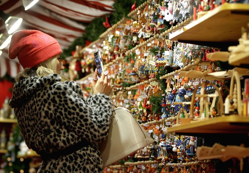 A visitor takes photos of Christmas ornaments at the Vancouver Christmas Market at Jack Poole Plaza in Vancouver, Canada.