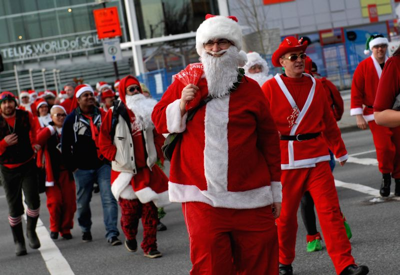 People dressed in Santa costumes cross the street in Vancouver for the annual SantaCon  festivities on Dec.13, 2014. SantaCon is an annual mass gathering of people dressed in Santa Claus ..