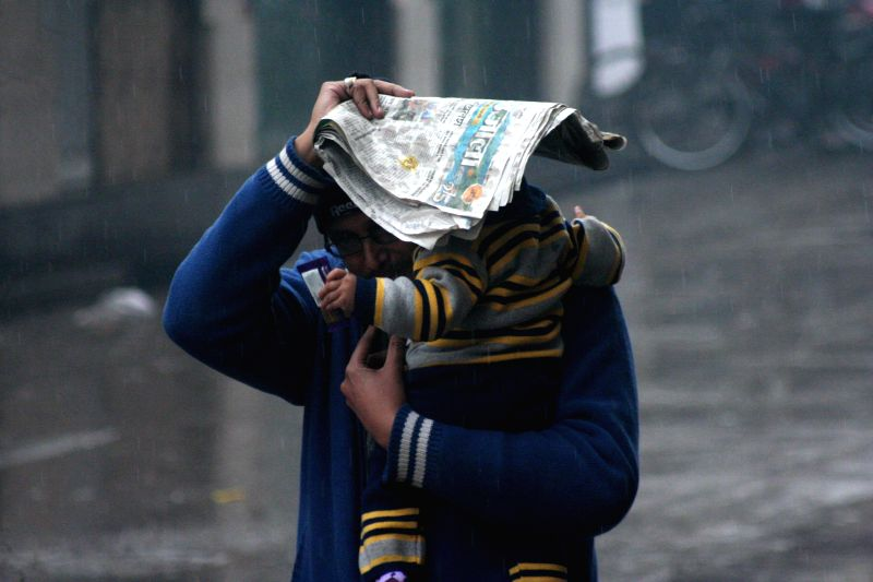 A man uses a newspaper to prevent a child from winter rains in Varanasi on Jan 1, 2015.