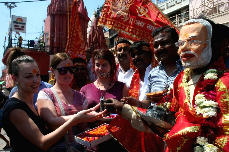 A man wearing the mask of Prime Minister Modi distributes sweets to foreigners on the eve of Hindu New Year in Varanasi on March 20, 2015. - Modi