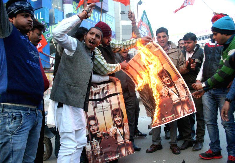 BJP workers burn a poster of Aamir Khan starrer film 'PK' outside a cinema hall in Varanasi, on Dec 31, 2014. - Aamir Khan