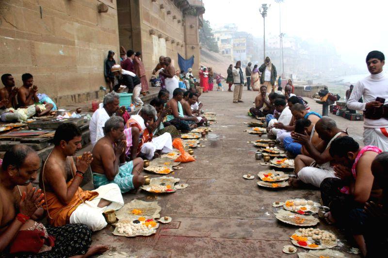 Devotees perform rituals on the banks of Ganga river on Makar Sankaranti in Varanasi, on Jan 14, 2015.