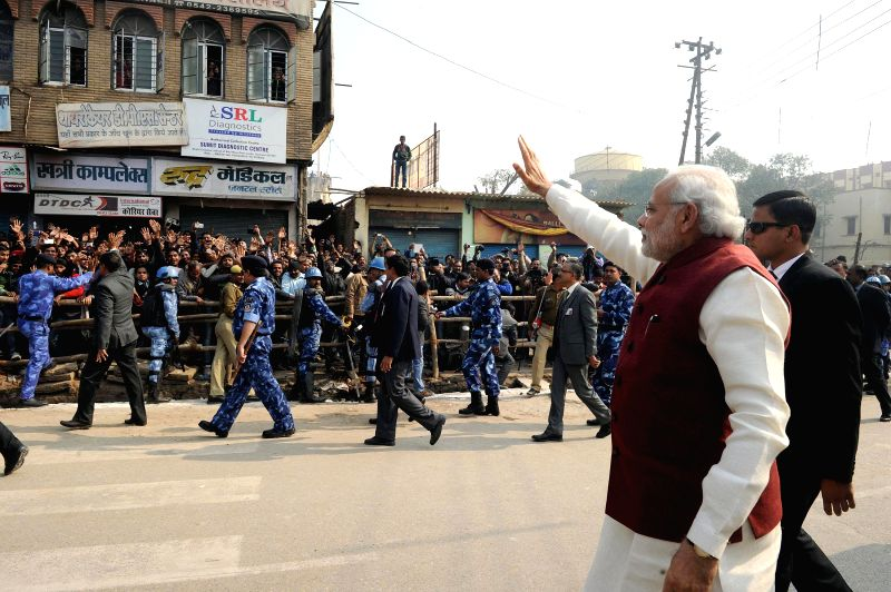 Prime Minister Narendra Modi greets people on the streets of Varanasi, Uttar Pradesh on Dec 25, 2014. - Narendra Modi