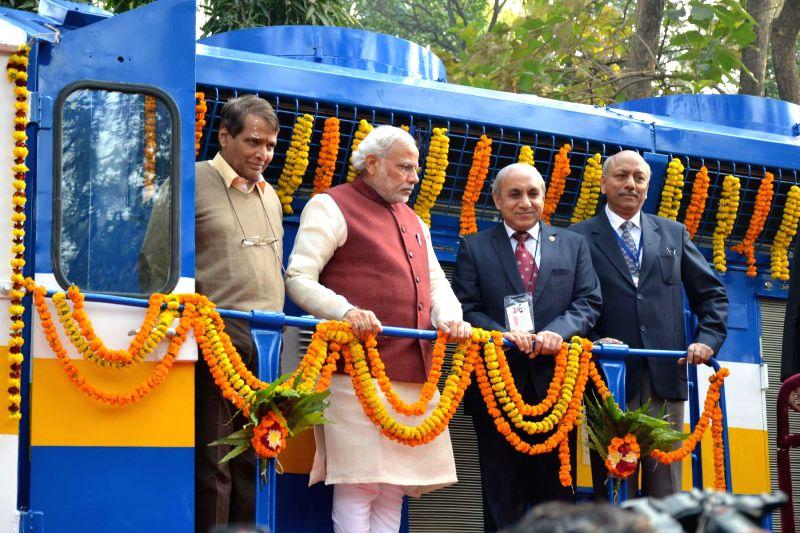 Prime Minister Narendra Modi on the new high horsepower diesel locomotive, at Diesel Locomotive Works (DLW), at Varanasi on Dec 25, 2014. Also seen  Union Minister for Railways Suresh ... - Narendra Modi, Suresh Prabhakar Prabhu and Board Arunendra Kumar