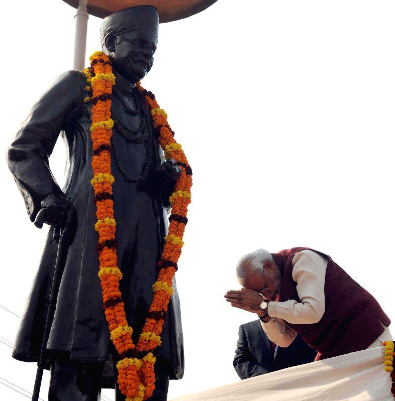 Prime Minister Narendra Modi pays homage at the statue of Pt. Madan Mohan Malavia, at Lanka Chauraha, in Varanasi, Uttar Pradesh on Dec 25, 2014. - Narendra Modi