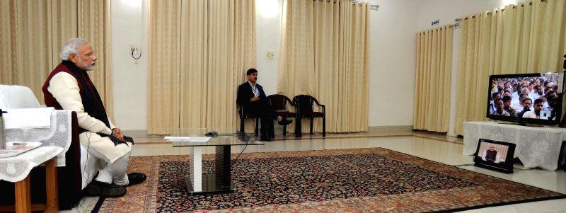 Prime Minister Narendra Modi video-conferencing with unorganised sector workers at 20 locations in Gujarat from Varanasi, Uttar Pradesh on Dec 25, 2014. - Narendra Modi