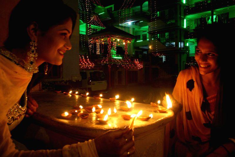 Women light earthen lamps on Diwali in Varanasi