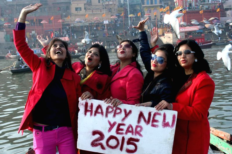 Women welcome 2015 aboard a boat on the Ganga river, near Dashashwamedh Ghat in Varanasi, on Dec 31, 2014.
