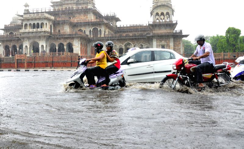 Vehicles find it hard to move on a flooded street of Jaipur on July 17, 2014.