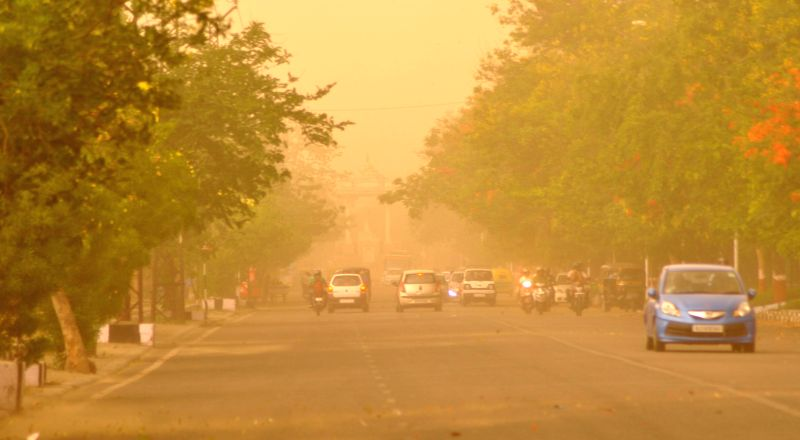 Vehicles move on a road during a dust storm in Jaipur on May 11, 2014.