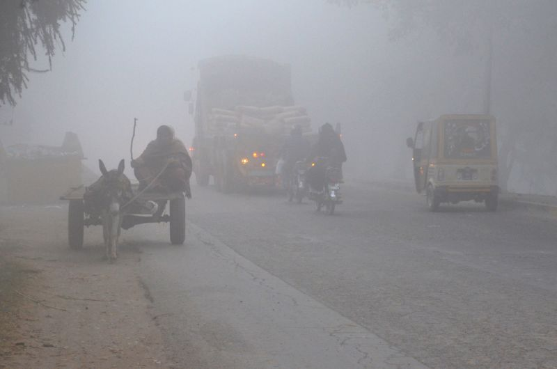 Vehicles move on road during heavy fog in Lahore, eastern Pakistan, Dec. 8, 2015. Dense fog covered several cities of Pakistan?s Punjab province, causing problem in ...