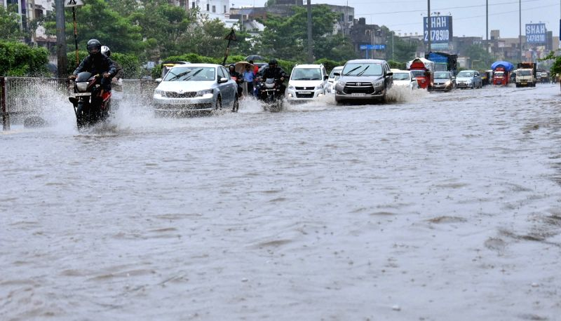 Vehicles move through a water-logged street after heavy rains lashed Ahmedabad on July 12, 2018.