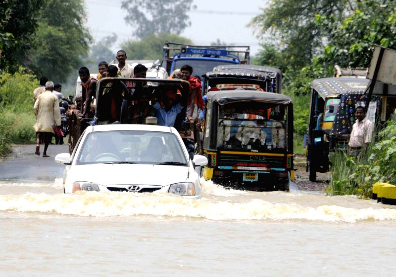 Vehicles ply on a road in flood affected Patna district of Bihar on Aug 19, 2014.