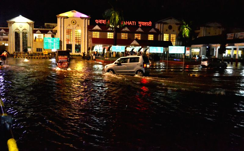 Vehicles ply on a water logged street in front of Guwahati Railway Station after heavy rains in the city on June 20, 2014.
