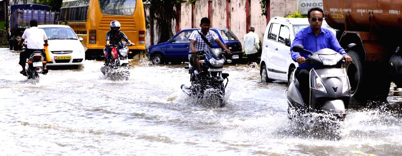 Vehicles ply on a waterlogged road in Sivasagar on July 2, 2014.