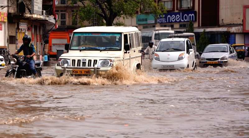 Vehicles ply on a waterlogged road of Jaipur after heavy rains on July 28, 2014.