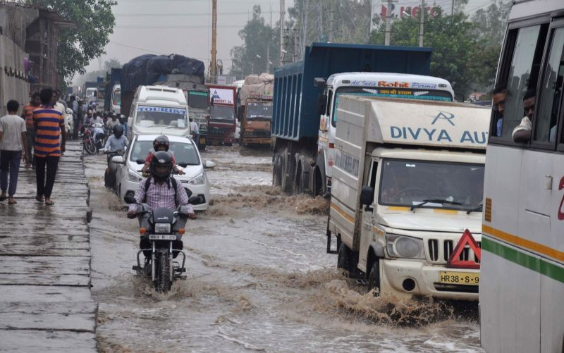 Vehicles ply on water logged roads of Gurgaon on July 26, 2016.