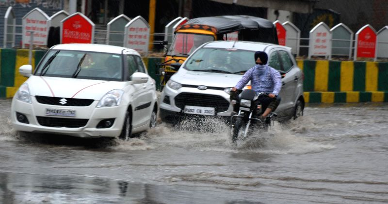 Vehicles ply on waterlogged streets of Amritsar after rains on June 25, 2014.